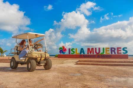 미소하고 행복 한 커플 Isla Mujeres, 멕시코에 열 대 해변에서 골프 카트를 운전