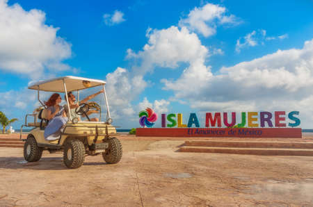 Smiling and happy couple driving a golf cart at tropical beach on Isla Mujeres, Mexico