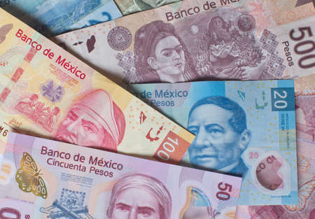 Different Mexican money bills stacked over each other forming a money background. Stock Photo