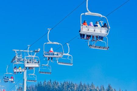 Bukovel, Ukraine - December 31, 2015: Skiers and snowboarders on a ski lift in Bukovel. Bukovel is the most popular Ukranian mountain resort. Editorial