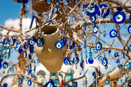 A nazar, charms to ward off the evil eye , on the branches of a tree in Cappadocia, Turkey