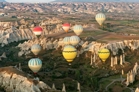 Colorful hot air balloons over mountain landscape in Cappadocia, Goreme National Park Turkey.