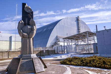 Chernobyl Exclusion Zone, Ukraine - February 23, 2019: Monument, fourth reactor and its enclosing sarcophagus.