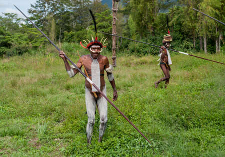 Papua Province, Indonesia -December 28, 2010: Unidentified warriors of a Papuan tribe in traditional clothes are having a demonstration of war skills at New Guinea Island