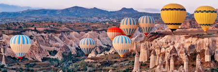 Wide landscape with colorful hot air balloons flying over mountain landscape in Cappadocia, Goreme National Park, Turkey.