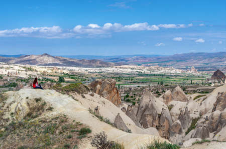 Traveler against the background of mountains landscape with geological structures in Cappadocia, Central Anatolia, Turkey