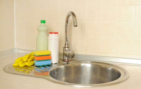 Detergent bottles and sponges near the faucet in the kitchen Stock Photo - 16279327