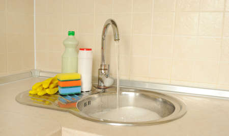 Detergent bottles and sponges near the faucet in the kitchen Stock Photo - 16279329