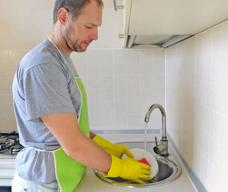 Man washing dish in the kitchen photo