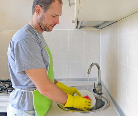 Man washing dish in the kitchen
