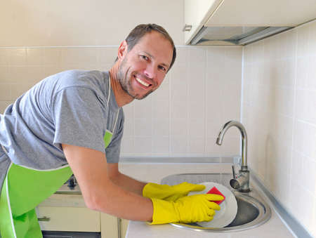 Smiling man washing dish in the kitchen