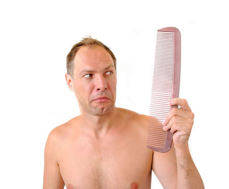 befuddled: Surprised man hand holding comb near the head
