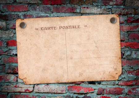 Carte postale with button on a brick wall Stock Photo - 16910458