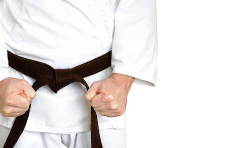 arts backgrounds: Man in a kimono and belt for martial arts on the white background