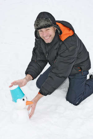 Smiling man sculpts snowman with blue bucket Stock Photo - 17342207