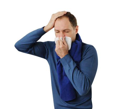 cold season: Man blowing his nose and holding his head isolated on white background