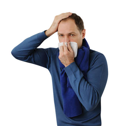 suffer: Man blowing his nose and holding his head isolated on white background