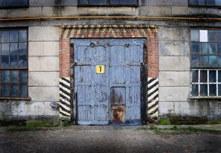 Vintage old factory with closed door and windows photo