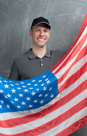 Smiling man in gray against background of the USA flag photo