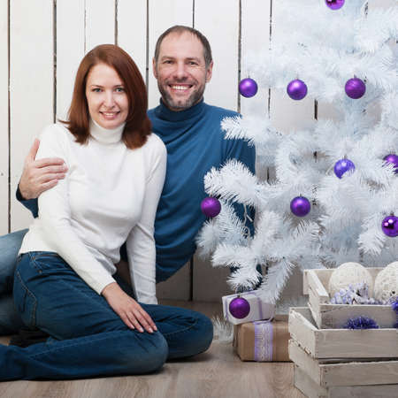 Smiling couple near a Christmas tree photo