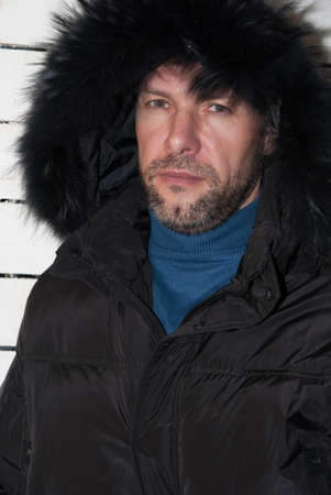 parka: Portrait of confident man wearing fur hooded parka coat at the white wall Stock Photo
