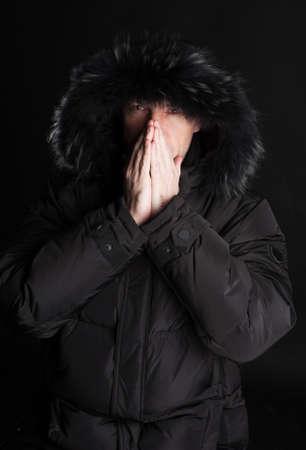 Frozen man in black alaska warming his hands photo