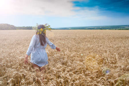 Beautiful girl in  wreath in the field of ripe wheat with lens flare effect photo