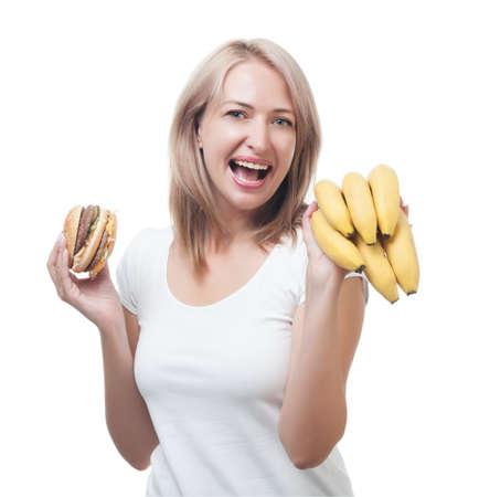 Woman  makes choosing burger and bananas photo