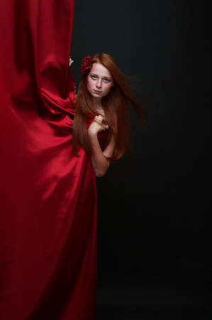 carmen: Beautiful red-haired girl looks out from behind a red theater curtain