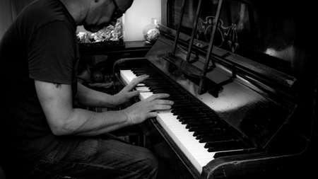 Black and white image of a person playing an old piano