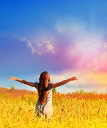 Free happy woman enjoys freedom on sunny meadow. Nature. Imagens