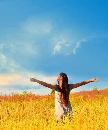 Free happy woman enjoys freedom on sunny meadow. Nature. Фото со стока