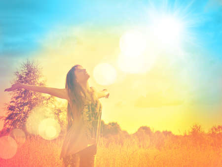 햇빛에 햇볕이 잘 드는 풀밭 입욕에 자유를 즐기고 행복 한 젊은 여자