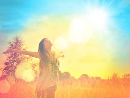 Happy jonge vrouw genieten van de vrijheid op een zonnige weide baden in het zonlicht Stockfoto