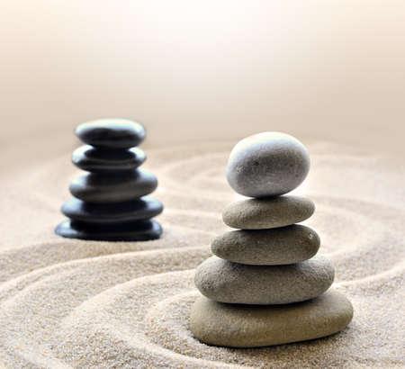 raked: White pebbles stones stacked inside raked circle in zen garden with black stones outside