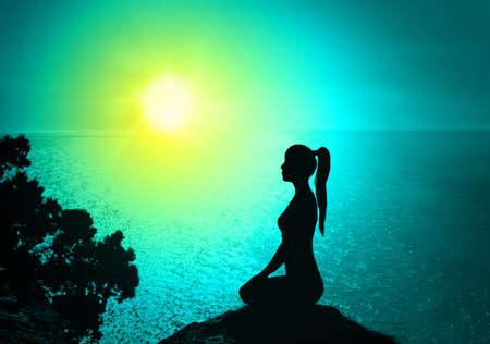 Silhouet van een vrouw op het strand van sunrise.Yoga en meditatie. Stockfoto
