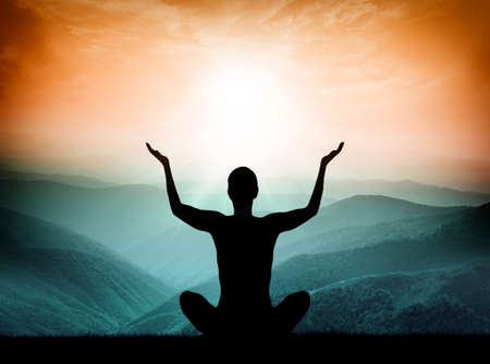 poses: Yoga and meditation. Silhouette of man on the mountain.