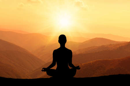 man meditating: Man meditating in yoga position on the top of mountains Stock Photo