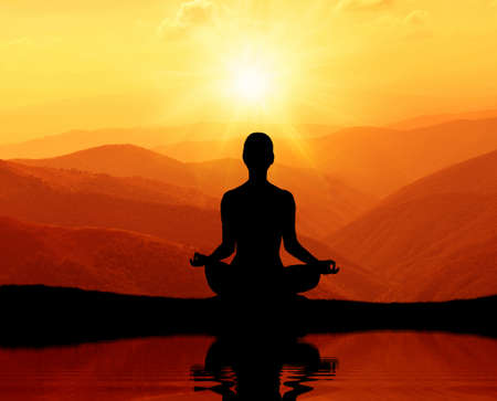 meditation woman: Man meditating in yoga position on the top of mountains Stock Photo