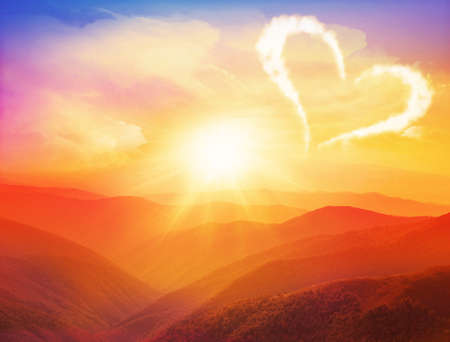Majestic sunset in the mountains landscape with hearts and Valentines day Reklamní fotografie