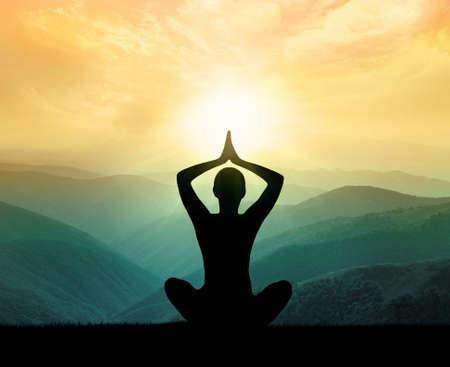 El yoga y la meditación. Silueta del hombre en la montaña Foto de archivo - 43970552