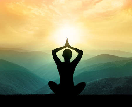 mind body soul: Yoga and meditation. Silhouette of man in the mountain