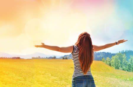openness: Young girl spreading hands with joy and inspiration facing the sun