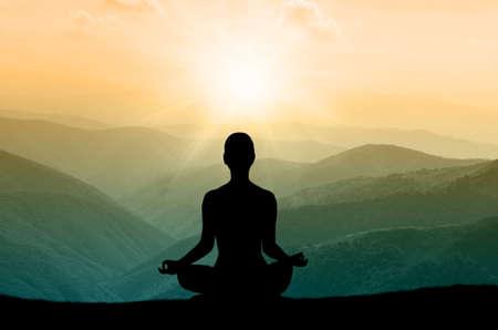 armonia: Silueta de la yoga en la montaña en los rayos del sol. el sol del amanecer Foto de archivo