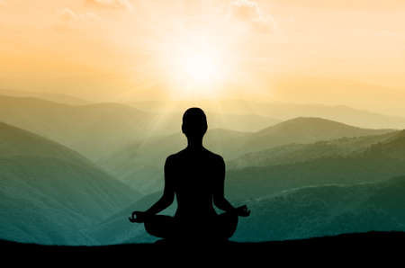Yoga silhouette on the mountain in sunrays. the dawn sun Stock Photo