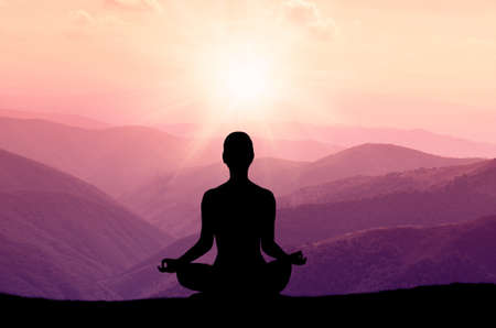 positions: Yoga silhouette on the mountain in sunrays. the dawn sun Stock Photo