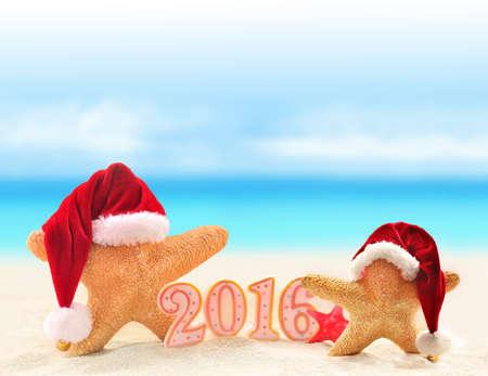Nieuwe jaar 2016 teken met zeester in Santa Claus hoed op een strand zand