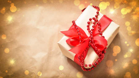 red gift box: Gift box tied red ribbon on old wooden background. Stock Photo