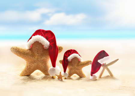 christmas greeting: Starfish on summer beach and Santa hat. Merry Christmas.