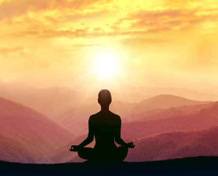Silhouette of a woman practicing yoga in the mountains at sunrise Standard-Bild